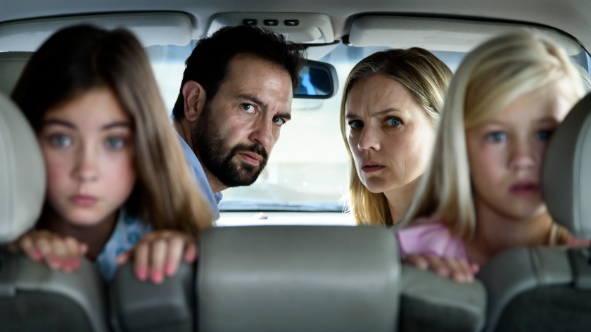 A scene from Tailgate in which a family, sat in a car look behind them